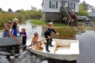 3rd PLACE SPOT NEWS: Jonathon Gruenke, Daily Press---Ryan West, center, paddles a boat with other children through rising flood water in Poquoson Saturday afternoon October 3, 2015.