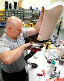 Prosthetist Joe Sullivan makes adjustments to University st of Virginia student coach Jacob Rainey's running prosthesis. Rainey was a quarterback for Woodberry Forest when his leg had to be amputated after a severe injury.