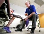Prosthetist Joe Sullivan adjusts triathelete Robin Yoder's prosthesis as she tries out a Triton smart ankle at Powell Orthotics and Prosthetics.