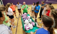 James River Head Coach Joe Sullivan, middle, goes over some pointers with his volleyball team during practice.