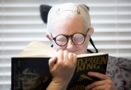 Tonya Davison, 36, has two sets of glasses - one for reading and one for distance. Here Tonya tests her new reading glasses by reading a book from her favorite author, Stephen King, comfortably at Dr. David Armstrong's office in Roanoke.