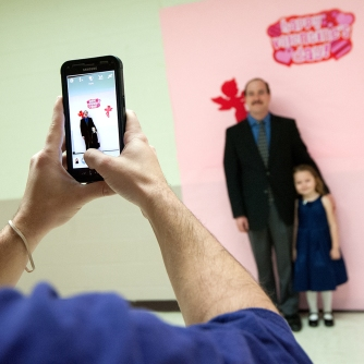 Mike Love, of Harrisonburg, stands with his daughter, Aubrey, 4, as they get their photo taken by Danny McDonald, a 20-year-old Harrisonburg Parks and Rec worker and JMU student of Richmond.
