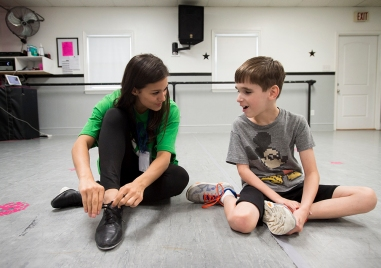 "Volunteer Ally Nigro helps Jordan East put on his tap shoes during Forest Dance Academy's Superhero Dance Camp. The week long camp is for students with disabilities such as cerebral palsy, in wheelchairs, down syndrome and autism. It focuses on different types of dance, movements and rhythm. ""I think they are getting some great therapy both physically and emotionally and they don't even know it because they are having a blast doing it,"" said director Michelle Thomas."
