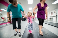Madison Rodgers walks with her mom Amber (right) and volunteer Jennifer Younce during the Superhero Dance Camp for children with special needs at the Forest Dance Academy. Rodgers has cerebral palsy and has to use a walker to get around on her own.
