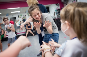 Volunteer Zoie Younce dances with Emily Woodall during Superhero Dance Camp.