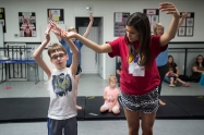 Volunteer Ally Nigro helps Jordan East perform a dance move during Superhero Dance Camp.