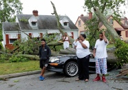 Ameyah Graves (far left) couldn't believe that her mother's car was totaled by a fallen tree during Thursday night's storm. She and neighbors along Patrick Avenue lost their power. From left: Ameyah Graves, Jamya Mobley (11), Aquan Mobley (7), their mother Audreyel Mobley and Audreyel's husband, Jonas Baptist. June 17, 2016.