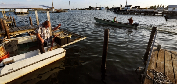 Rudy Shores waves to a passing boat while he works from his work shanty in the evening of Wednesday, Aug. 10. Local watermen make a living crabbing for Chesapeake blue crab in the summer and oysters in the winter.