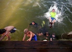 "A group of local children meet at the ice cream shop and walk over to the docks at 5 p.m. everyday. They spend the next few hours climbing and jumping off the wooden docks, swimming with the ""water gulls"" or jellyfish, hoping not to get stung. Thursday, Aug. 11, 2016."