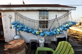 Colored crab pot buoys hang from a line outside of the mayor's work shanty off Tangier Island. The island is a working watermen village which draws leagues of tourists ferried in from the mainland every summer for fresh, locally caught Chesapeake blue crab and laid-back lifestyle. Wednesday, Aug. 10, 2016.