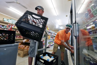 Owners Terry, left, and Lance Daley, right, stock cooler units at Daley & Son Grocery store on Tangier Island. The island has one grocery store and residents must place orders for specialty items to be brought in on the ferry. Friday, Aug.12, 2016.