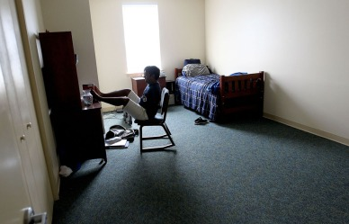 Christopher Newport student James Dennehy gets his book ready for class in the dorm he shares with two other roommates.