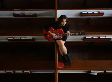"Angelica Garcia sits with her guitar on the box pews in the sanctuary of St. James Church in Accomac, Va. on Thursday, Sept. 8, 2016. Garcia will have her debut album ""Medicine For Birds"" released on Sept. 30th. Garcia wrote the majority of her songs in the church's nearby rectory and parish house. Her single ""Orange Flower"" has been featured on NPR."