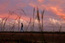 Bobby Autry walks along Museum Parkway as the sun begins to set over the James River Tuesday evening October 4, 2016.
