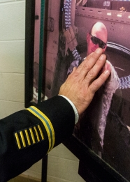 "(20161104) - (Broadway) Army Captain John Baer touches a photo of former Broadway football player Brian ""Bucky"" Anderson as he leaves the Broadway High School locker room. Baer was Anderson's platoon leader when the Broadway native was killed in action in an IED attack in Afghanistan in 2010."