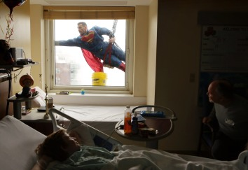 1st Place Feature:Vicki Cronis-Nohe, Virginian-Pilot--Patient John Geheren, 11, and his father Michael, right, watch in surprise from a hospital room as Wayne Barrows swings by their window on March 21, 2016. The crew of Appearances Window Cleaners of Tidewater dressed as superheroes as a treat for patients at the children's hospital in Norfolk.