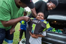 2nd Place Sports Feature: Bill Tiernan, Virginian-Pilot--From left: Coach Leon Wilson jokes with Kemon Wood,4, who plays with the super tiny mites football team of the 757 Seahawks Youth Athletic Association, after he put his shoulder pads on backwards before a team practice Sept.29, 2016. His father Detrell Wood, an assistant coach of the super tiny mights, was helping his son get his pads turned around. Wilson is a coach of the 10U division players.