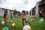 3rd Place Feature: Erica Yoon, Roanoke Times--Maria Goodman-Osby, 5, center, plays with inflated beach balls along with other community members at Afton Garden Apartments off of Hunt Ave. NW during National Night Out on Tuesday, Aug. 2, 2016. Part of the night's mission is to foster community building and promote police-community partnerships.