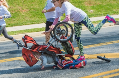 3rd Place Spot News: Lee Luther--The front wheel came off of Susan Malburg's stroller tipped over but the baby and Malburg were not hurt as both were quickly cared for by other runners in the IRON 5 K Race on Sunday.