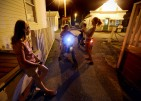 Local children hang out in an alley way with their motorized scooters as night falls on Tangier Island on Thursday, Aug. 11, 2016.