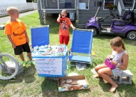 Derek Barbee, 11, left, looks at his brother Scott, 9, center, while Dakota Dunivan, 10, right, counts change for a customer while they sell hand-made items to tourists who visit Tangier Island on Wednesday, Aug. 10 2016.