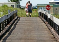 While crossing a wooden bridge a couple holds each other as they walk on a sunny day on Tangier Island. Wednesday, Aug. 10, 2016.