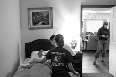 "HM Feature Picture Story: Jonathon Gruenke, Daily Press--Bradley Garner, center, and Frankie Garner stand beside their father, Jim Garner, while he lies in bed at Commonwealth Assisted Living in Hampton as Karen Garner responds to messages on her phone Thursday evening March 24, 2016. Jim died from Alzheimer's April 2, 2016. Jim was diagnosed by the National Institute of Health in 2011 with ""mild cognitive impairment,"" the precursor to early-onset Alzheimer's disease. The genetically pre-determined disease has devastated his family--his mother died of the disease at age 61, his older brother at 52."