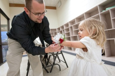 HM Feature Picture Story: Nikki Fox, Daily News Record--Eric Oberg, of Verona, puts a corsage on his 2-year-old daughter, Alyssa, as they arrive to the annual Daddy Daughter Sweetheart Dance at the Cecil F. Gilkerson Community Activities Center Saturday night, Feb. 6, 2016.