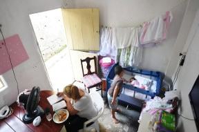 Severina Carla da Silva, eats while writing down song lyrics as her son, Nicolas Davi Silva, 5, looks at his sister, Nivea Heloise Silva at their home on Tuesday March 15, 2016 in Recife, Brazil. Nivea was born with microcephaly. The Zika virus is linked to the condition.