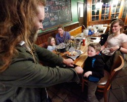 Peter Hoskins plays a game with Cian Duffy, age 7, at Green Leaf Cafe in Williamsburg after Hoskins' team, Richmond Battery GAA, played the Hampton Roads Hurling Club at the James City County Recreation Center field Saturday, February 20, 2016. In the background are, left to right, Ella Duffy, age 4, Corey Delaney and Emily Delahunty.