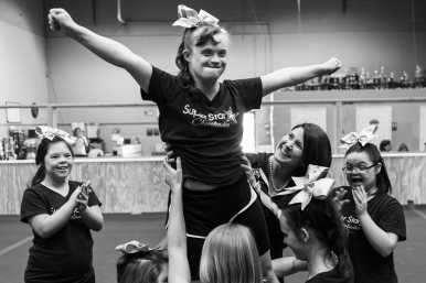 3rd Place Sports Picture Story: Lathan Goumas, News & Advance-- The Dynamic Cheer Super Stars are a special needs competitive cheer team founded by Billie Wray Nuckols because of her daughter's, Jodie, interest in cheering. In the two years since beginning, the team has be designated as an All Star team by the United States All Star Federation of Cheer and Dance Teams and won a national championship. The team brings together girls with a variety of special needs including ADHD, Aspergers and Down syndrome. The team practices twice a week nearly year round. Kaitlin Elliott, 18, is lifted by her Dynamic Cheer Super Stars teammates as they practice a new stunt on Saturday April 2, 2016 in Lynchburg, VA. The Dynamic Cheer Super Stars are a special needs competitive cheer leading team. The team was founded two years ago by Billie Wray Nuckols, who has a daughter on the team.