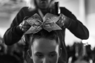 "Haley Coleman, 15, gets her hair done by Angela Hamilton before the Dynamic Cheer Super Stars perform at the Cheer and Dance Extreme Finale on Saturday April 9, 2016 in Virginia Beach, VA. ""The girls care for each other,"" said Hamilton, whose 13-year-old daughter, Kirsten, is on the team. ""They take cues from one another. They know when somebody's having a good day. They know when somebody's having a bad day."""