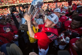 Western Kentucky quarterback Brandon Doughty (12) is raises the Conference USA trophy after beating Southern Mississippi in the Conference USA football Championship game between WKU and Southern Mississippi University on Saturday Dec. 5 at L. T. Smith Stadium in Bowling Green, Ky.