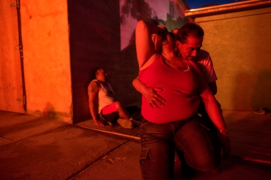 Dina Ponce is held by her boyfriend as they watch their homes burn down on Saturday June 26, 2016 in the Gamerco neighborhood on in Gallup, Nm. Ponce's trailer burned along with her bother's but her daughter's, Janelle Trujillo, home survived.
