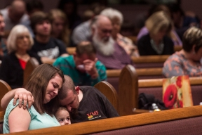 "Cody McCune wraps his arm around his wife Brittany McCune as their daughter Meadow,3, sits between them during a service at Evergreen Baptist Church marking the one year anniversary of a tornado on Thursday Feb. 23, 2017 in Appomattox, Va. ""We're slowly getting back on our feet,"" Cody McCune said of the family, who lost their home in the storm."