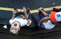 Zackary Reynolds, 9, left, attempts to catch a piece of popcorn in his mouth after the Peninsula Pilots season opener was cancelled due to a severe thunderstorm on Wednesday, May 31, 2017.