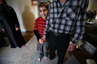 Zahra Almahdi, left, stands in the background as Mohamad, 9, holds his father's hand, Abdul-Kareem Almahdi, right, in the living room of their home in Newport News. Originally from Raqqah, Syria, the family spent four years living at a refugee camp in Jordan before being relocated to the United States. Almahdi works the night shift at a pharmaceutical company in Williamsburg and only sees his family for a small portion of the day.