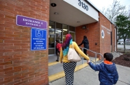 Local Syrian refugee family aid Rabia Jafir, left, holds hands with Laith Almahdi, 5, right, while entering the Hampton Health Clinic. Jafir helps the family by driving the children to various appointments, like immunization shots, since their mother is not licensed to drive and the father works long night shifts. The family previously had current vaccines while living in Syria but the recent move to United States required new documentation under U.S. law. Friday, March 10, 2017.