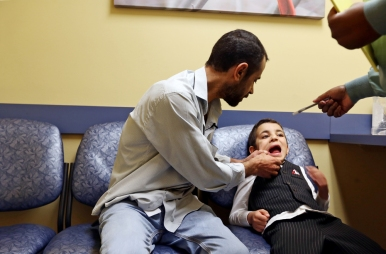 Abdul Kareem Almahdi, left, holds the mouth of his youngest son, Laith, 5, to show the dental assistant new teeth growth during an appointment on Thursday, March 30, 2017. Originally from Raqqah, Syria, the family spent four years living at a refugee camp in Jordan before being relocated to the United States. Located in the north eastern part of Syria and seized by militants in late 2013, the city the family once lived, is now the capitol of the Islamic State.
