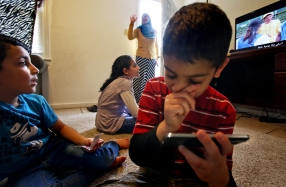 The Almahdi children watch television captioned in Arabic as Rabia Jafir, center, waves goodbye to the family after a visit on Friday, March 10, 2017. Jafir acts as a family aid to multiple Syrian refugee families living in Newport News, assisting them with everyday adjustments to their new American life.