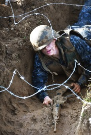 "ANNAPOLIS, MD - May 16: A Naval Academy plebe goes through the trench area that is part of the ""Wet and Sandy"" portion of the annual Sea Trials at the United States Naval Academy on Tuesday May 16, 2017 in Annapolis, MD."