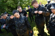 "ANNAPOLIS, MD - May 16: Naval Academy plebe, Grace Rovira, left center, wipes off her face after taking part in the ""Wet and Sandy"" portion of the annual Sea Trials at the United States Naval Academy on Tuesday May 16, 2017 in Annapolis, MD."