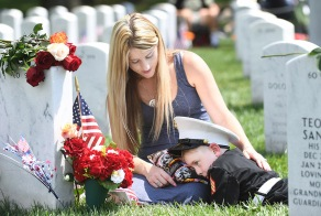 ARLINGTON, VA - May 29: Brittany Jacobs sits with her son, Christian Jacobs, 6, near the grave of Christian's father, U.S. Marine Corps Sgt. Christopher James Jacobs as they visit in observance of Memorial Day at Arlington National Cemetery on Monday May 29, 2017 in Arlington, VA. Jacobs died during a training exercise in 2011.