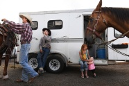 Evan Koster attends to his horse while standing next to J.D. Slagowski as Evan's wife, Maggee Koster holds their daughter, Raelyn Koster, 1, prior to the start of the Snowmass Rodeo on Wednesday July 19, 2017 in Snowmass Village, CO. This is the 44th year for the weekly rodeo that runs from mid-June through August.