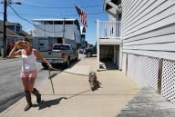First Hand Stasia Hudson, walks along the sidewalk with Pig as she waits for the boat to be unloaded at L D Amory & Company fish market in downtown Hampton. The 1 1/2-year-old potbelly pig is the resident pet of the ship and lives on the Carol Ann, a longline fishing boat, with the crew members while at sea. Wednesday, June 21, 2017.