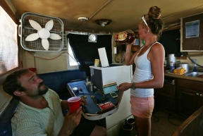 """Captain Todd Beland, left, watches as First Hand Stasia Hudson, takes a swig of whiskey from the bottle as they wait for their catch to be processed in Hampton. Beland sits in the booth where the body of their 5th crew member, Timmy, laid for about an hour after overdosing while out at sea. """"Can't no-one hide from it"""". Hudson says. Beland doesn't allow use of drugs or alcohol until the ship is docked but couldn't help his 5th crew member that night."""