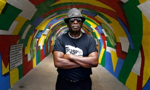 Artist Sir James Thornhill stands in the newly unveiled mural honoring Arthur Ashe at the pedestrian tunnel to Battery Park on Wednesday July 12, 2017.