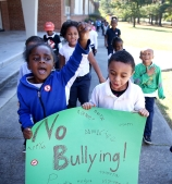 Rameer Battle (left) and Jordan Roney, both kindergarteners at Walnut Hill Elementary, lead a group of kids in a march around the school to protest bullying on Friday Oct. 27, 2017.