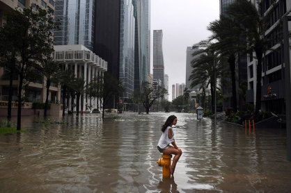 Mia Herman has an acquitance take a photo of her sitting on a fire hydrant on a flooded street as Hurricane Irma hits the area on Sunday September 10, 2017 in Miami, FL.