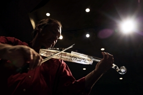 Artificial light beams through Dean Shostak's glass violin as he warms up for a show at the Williamsburg Library on Friday , Dec. 8, 2017. Shostak is a multi-instrumental musician who specializing in unique glass instruments. The glass armonica was invented by Benjamin Franklin in 1761 and composers such as Mozart and Beethoven wrote parts for the instrument.